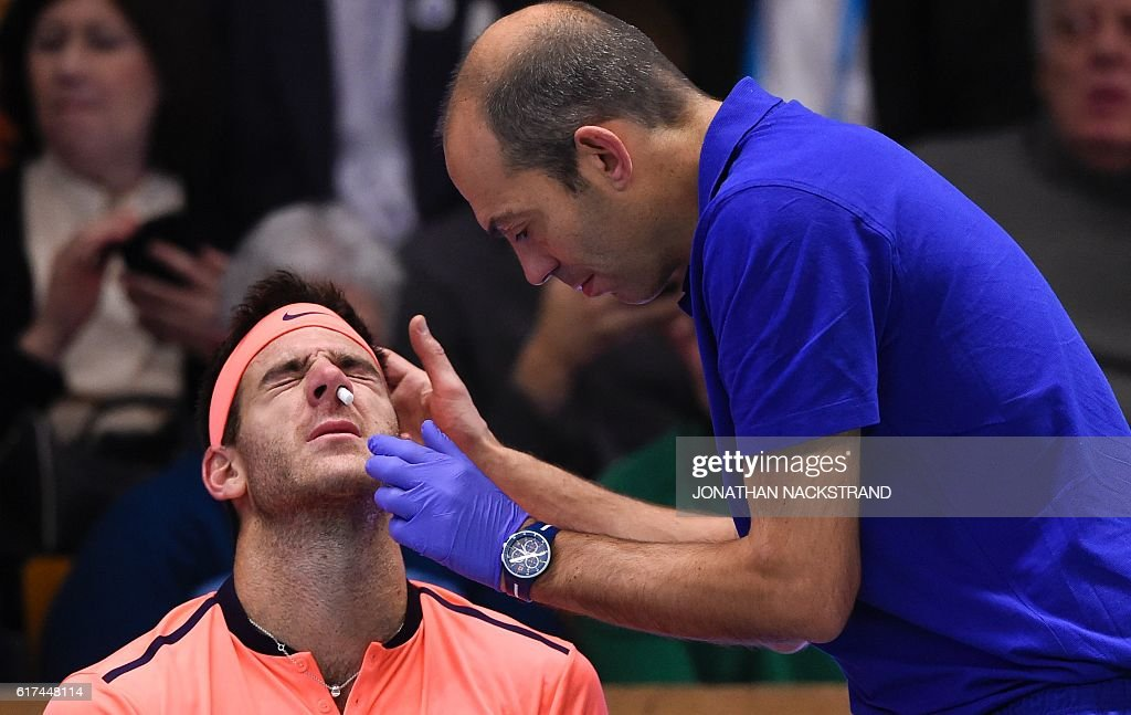 Argentina's Juan Martin Del Potro is treated for nose bleeding as he plays against USA's Jack Sock during the final match of ATP Stockholm Open tennis tournament in Stockholm on October 23, 2016. / AFP / JONATHAN