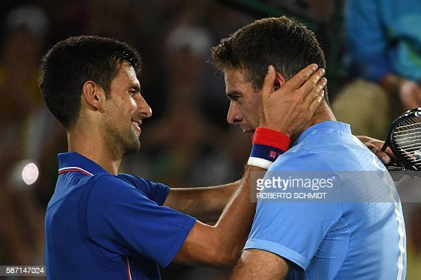 Argentina's Juan Martin del Potro speaks to Serbia's Novak Djokovic after winning their men's first round singles tennis match at the Olympic Tennis...