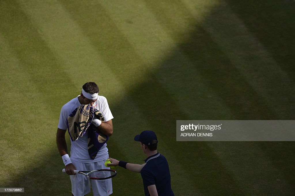 Argentina's Juan Martin Del Potro takes balls from the ballboy as he plays against Italy's Andreas Seppi during their fourth round men's singles match on day seven of the 2013 Wimbledon Championships tennis tournament at the All England Club in Wimbledon, southwest London, on July 1, 2013. Del Potro won 6-4, 7-6, 6-3.