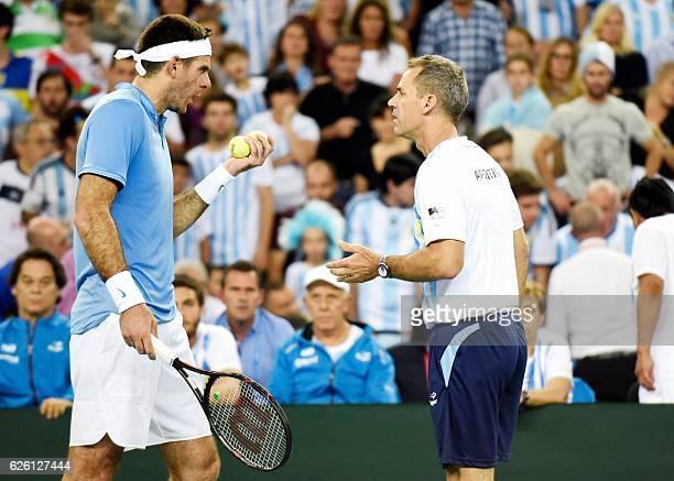 Argentina's Juan Martin del Potro talks with his head coach Daniel Orsanic Marin Cilic during the Davis Cup World Group final singles match between...