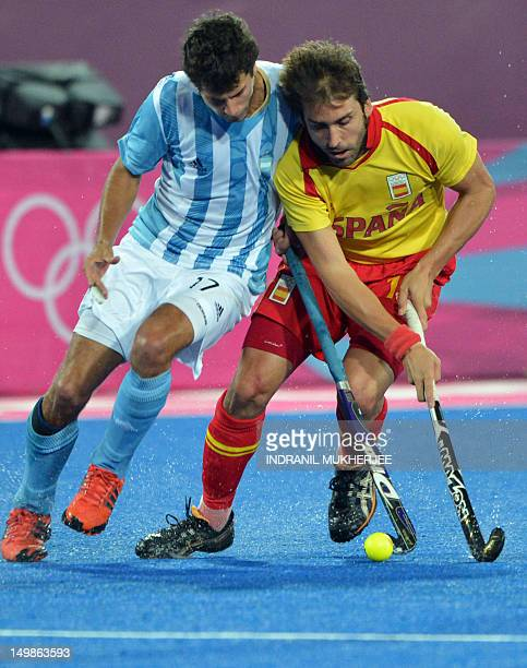 Argentina's Juan Martin Lopez tackles Spain's Eduard Tubau during the men's field hockey preliminary round match between Argentina and Spain at the...