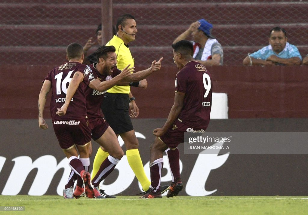 Argentina's Lanus forward Bruno Vides (R) celebrates with teammates forward Lautaro Acosta (C) and midfielder Gaston Lodico after scoring a goal against Peru's Sporting Cristal during the Copa Sudamericana 2018 first stage football match at 'La Fortaleza' stadium in Lanus, Buenos Aires, Argentina, on February 21, 2018. /