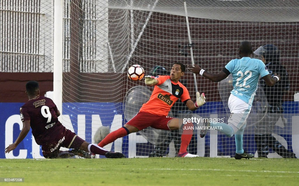 Argentina's Lanus forward Bruno Vides (L) strikes to score a goal against Peru's Sporting Cristal goalkeeper Patricio Alvarez (C) during their Copa Sudamericana 2018 first stage football match at 'La Fortaleza' stadium in Lanus, Buenos Aires, Argentina, on February 21, 2018. /