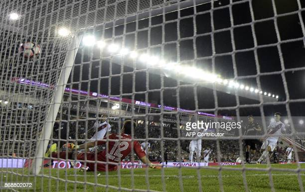 Argentina's Lanus forward Jose Sand strikes to score the team's first goal against Argentina's River Plate goalkeeper German Lux during their Copa...