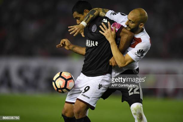 Argentina's Lanus forward Jose Sand vies for the ball with Argentina's River Plate defender Javier Pinola during their Copa Libertadores semifinal...