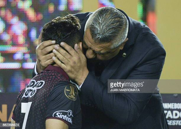 Argentina's Lanus forward Lautaro Acosta is embraced by AFA President Claudio Tapia during the award ceremony of the Copa Libertadores 2017 final...