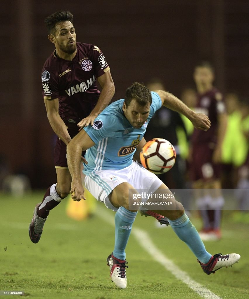 Argentina's Lanus forward Lautaro Acosta (L) vies for the ball with Peru's Sporting Cristal defender Renzo Revoredo during their Copa Sudamericana 2018 first stage football match at 'La Fortaleza' stadium in Lanus, Buenos Aires, Argentina, on February 21, 2018. /