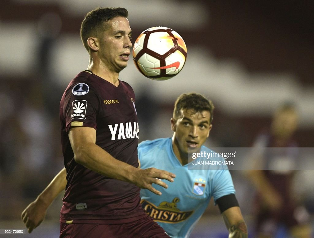 Argentina's Lanus midfielder Ivan Marcone (L) vies for the ball with Peru's Sporting Cristal forward Gabriel Costa during their Copa Sudamericana 2018 first stage football match at 'La Fortaleza' stadium in Lanus, Buenos Aires, Argentina, on February 21, 2018. /