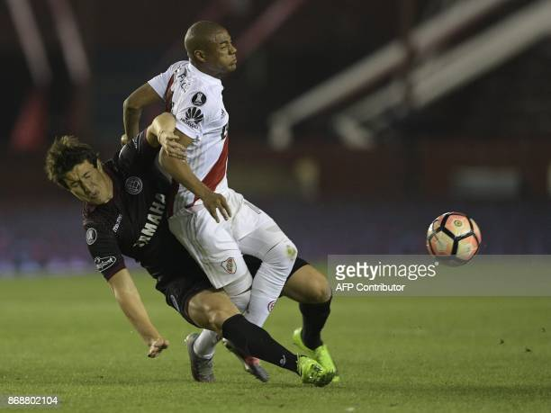 Argentina's Lanus midfielder Nicolas Aguirre vies for the ball with Argentina's River Plate midfielder Nicolas De La Cruz during their Copa...