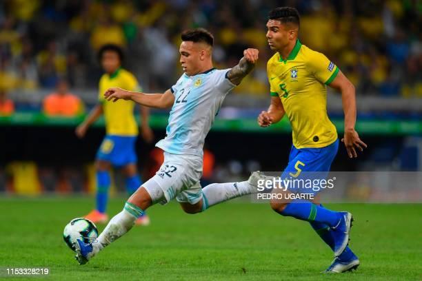 Argentina's Lautaro Martinez strikes the ball next to Brazil's Casemiro during their Copa America football tournament semi-final match at the...