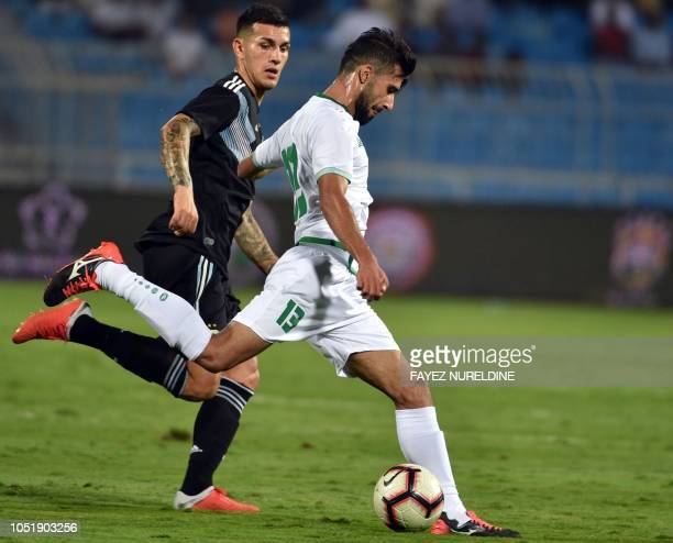 Argentina's Leandro Paredes marks Iraq's Bashar Rasan during a friendly football match between Argentina and Iraq at the Faisal bin Fahd Stadium in...