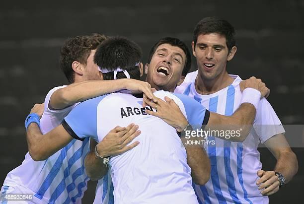 Argentina's Leonardo Mayer rcelebates with Carlos Berlocq and Federico Delbonis after winning the Davis cup semi-final tennis match against Belgium's...