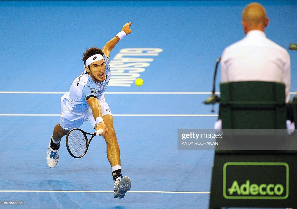 TOPSHOT - Argentina's Leonardo Mayer returns to Britain's Dan Evans during the Davis Cup World Group semi-final singles match 5 between Britain and Argentina at the Emirates Arena in Glasgow, Scotland, on September 18, 2016. / AFP / Andy Buchanan