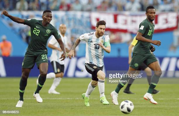 Argentina's Lionel Messi alongside John Obi Mikel and Kenneth Omeruo of Nigeria chases the ball during the first half of Argentina's 21 win in a...