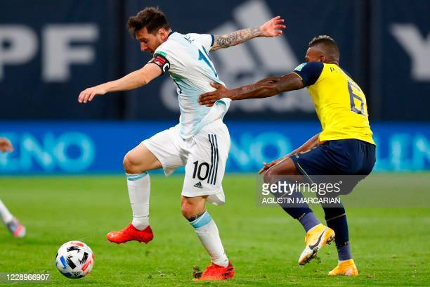 Argentina's Lionel Messi and Ecuador's Pervis Estupinan vie for the ball during their 2022 FIFA World Cup South American qualifier football match at...