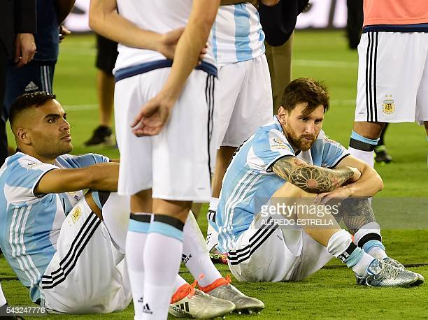 Argentina's Lionel Messi and Gabriel Mercado sit on the ground in dejection after being defeated by Chile in the penalty shootout of the Copa America...