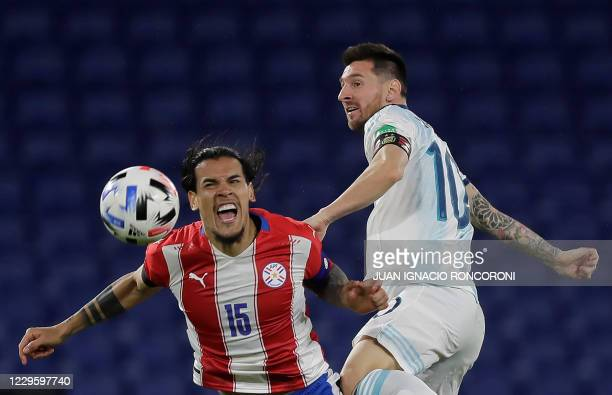Argentina's Lionel Messi and Paraguay's Gustavo Gomez vie for the ball during their closed-door 2022 FIFA World Cup South American qualifier football...