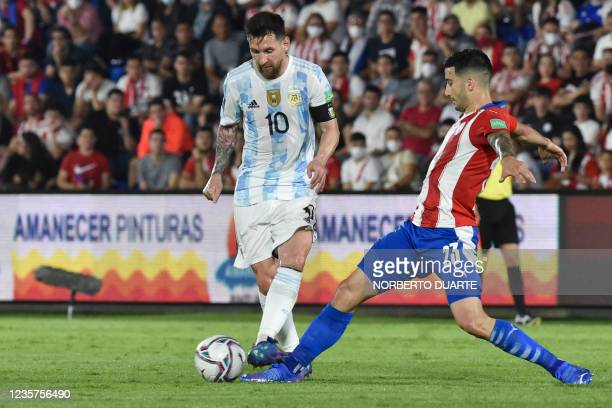 Argentina's Lionel Messi and Paraguay's Mathias Villasanti vie for the ball during their South American qualification football match for the FIFA...