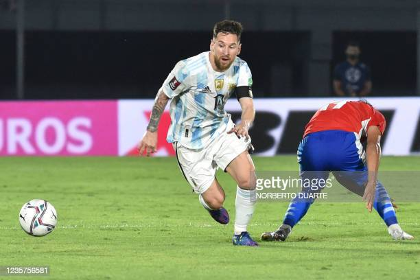 Argentina's Lionel Messi and Paraguay's Santiago Arzamendia vie for the ball during their South American qualification football match for the FIFA...