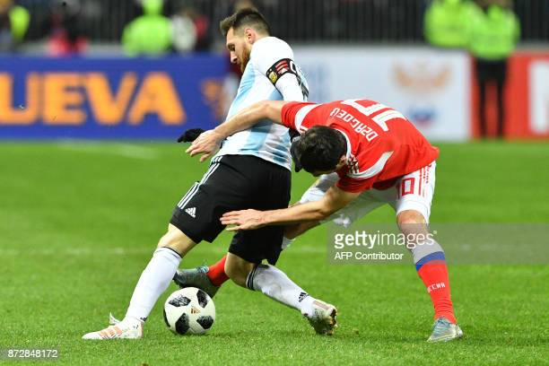 Argentina's Lionel Messi and Russia's midfielder Alan Dzagoev vie for the ball during an international friendly football match between Russia and...