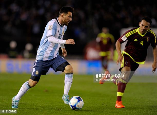 Argentina's Lionel Messi and Venezuela's Arquimedes Figuera vie for the ball during their 2018 World Cup qualifier football match in Buenos Aires on...