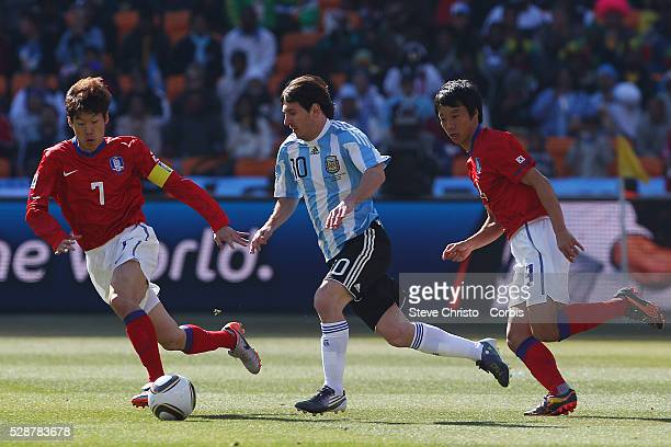 Argentina's Lionel Messi cuts across South Korea's captain Park JiSung and Yeom KiHun during the match at National Stadium Johannesburg South Africa...