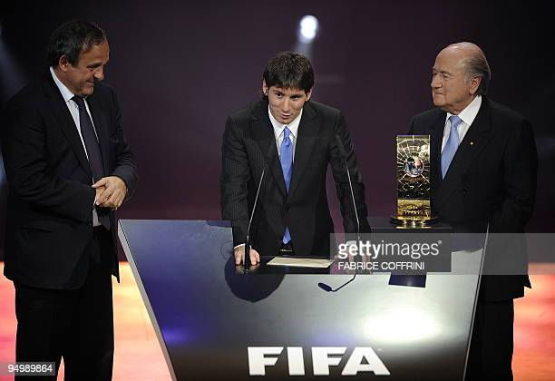 Argentina's Lionel Messi delivers a speech after he is awarded FIFA World Player of the Year as he is flanked by UEFA president French Michel Platini...