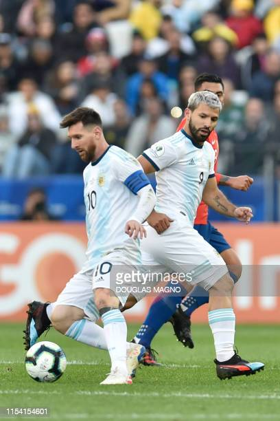 Argentina's Lionel Messi drives the ball as teammate Sergio Aguero looks on during their Copa America football tournament thirdplace match against...