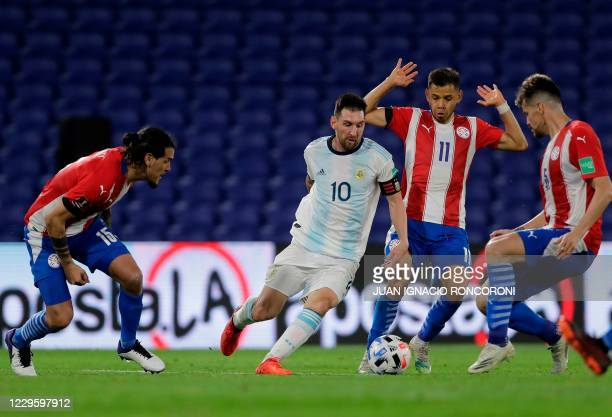 Argentina's Lionel Messi drives the ball next to Paraguay's Angel Romero during their closed-door 2022 FIFA World Cup South American qualifier...