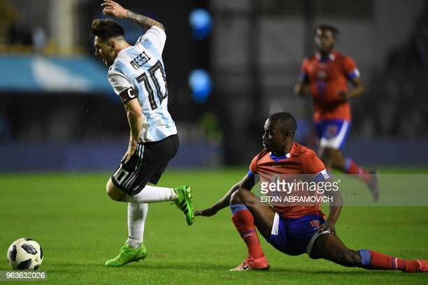 Argentina's Lionel Messi drives the ball past Haiti's Waldo Vernet during their international friendly football match at Boca Juniors' stadium La...