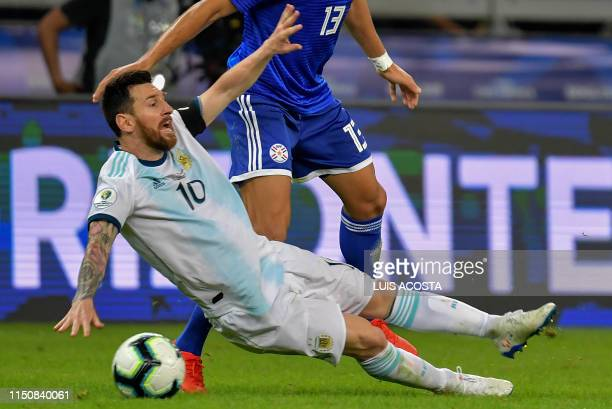 Argentina's Lionel Messi falls next to Paraguay's Junior Alonso during their Copa America football tournament group match at the Mineirao Stadium in...