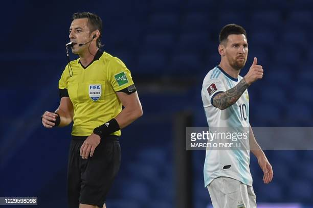 Argentina's Lionel Messi gives the thumb up next to Brazilian referee Raphael Claus during the closed-door 2022 FIFA World Cup South American...