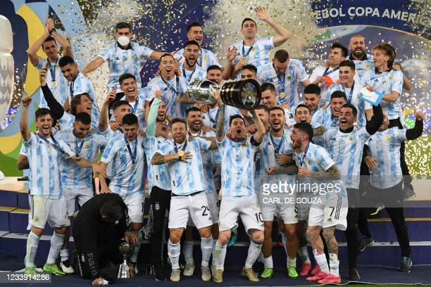Argentina's Lionel Messi holds the trophy as he celebrates on the podium with teammates after winning the Conmebol 2021 Copa America football...