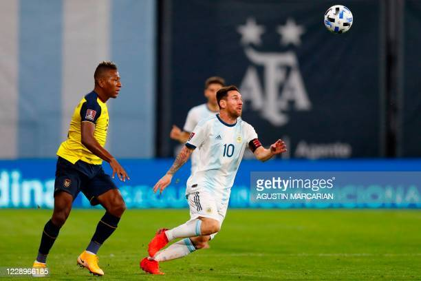 Argentina's Lionel Messi is challenged by Ecuador's Pervis Estupinan during their 2022 FIFA World Cup South American qualifier football match at La...