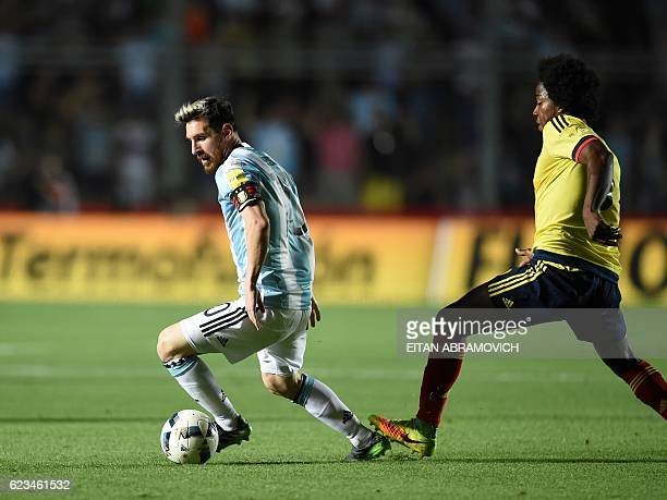 TOPSHOT Argentina's Lionel Messi is marked by Colombia's Carlos Sanchez during their 2018 FIFA World Cup qualifier football match in San Juan...