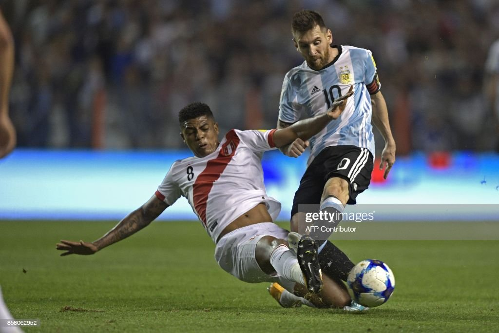 TOPSHOT - Argentina's Lionel Messi (R) is marked by Peru's Wilder Cartagena during their 2018 World Cup qualifier football match in Buenos Aires on October 5, 2017. / AFP PHOTO / Juan MABROMATA