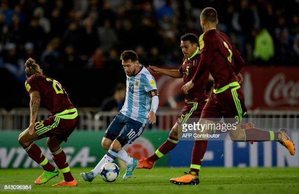 Argentina's Lionel Messi is marked by Venezuela's Rolf Feltscher Arquimedes Figuera and Mikel Villanueva during their 2018 World Cup qualifier...