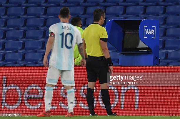 Argentina's Lionel Messi looks at Brazilian referee Raphael Claus checking the VAR during the closed-door 2022 FIFA World Cup South American...