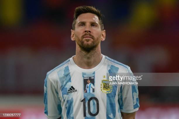 Argentina's Lionel Messi takes a picture of late Argentine football star Diego Armando Maradona on his jersey before the start of the South American...