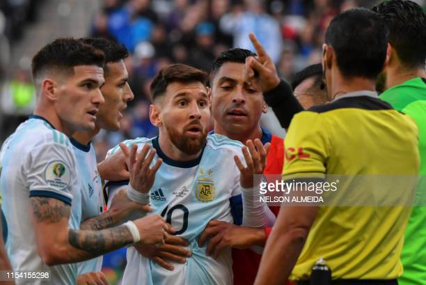 Argentina's Lionel Messi talks to Paraguayan referee Mario Diaz de Vivar after he and Chile's Gary Medel were sent off during their Copa America...