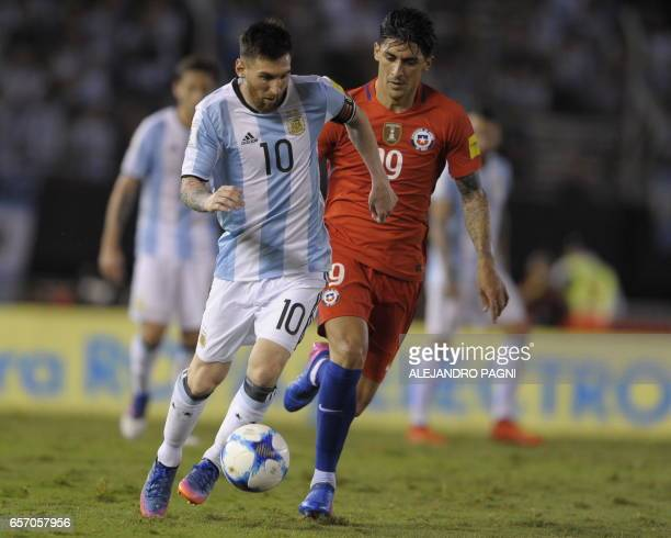 Argentina's Lionel Messi vies for the ball with Chile's Pedro Hernandez during their 2018 FIFA World Cup qualifier football match at the Monumental...