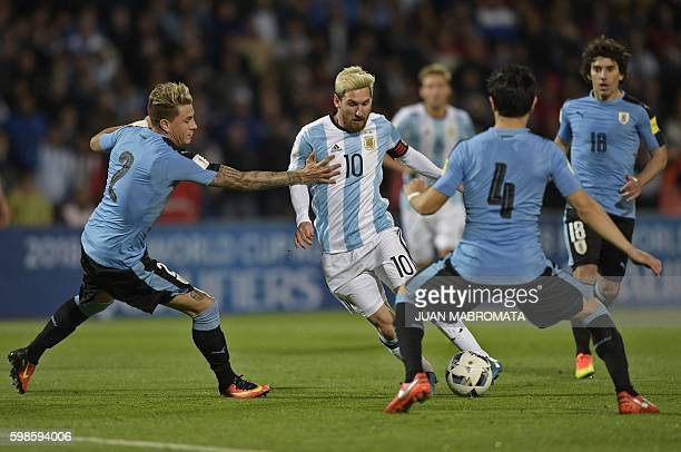 TOPSHOT Argentina's Lionel Messi vies for the ball with Uruguay's Jose Maria Gimenez and Uruguay's Jorge Fucile during the Russia 2018 World Cup...