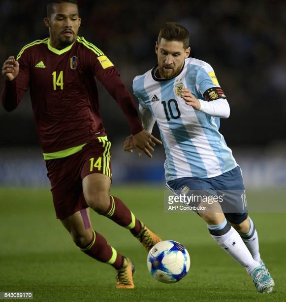 Argentina's Lionel Messi vies for the ball with Venezuela's Yangel Herrera during their 2018 World Cup qualifier football match in Buenos Aires on...
