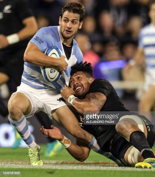 Argentina's Los Pumas flyhalf Nicolas Sanchez vies for the ball with New Zealand's All Blacks number Ardie Savea during their Rugby Championship...