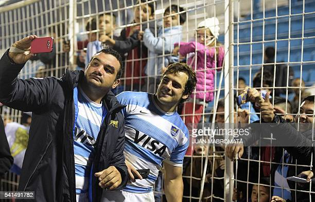Argentina's Los Pumas hooker Agustin Creevy and fly half Nicolas Sanchez pose for selfies with supporters after defeating 3019 France in their Rugby...