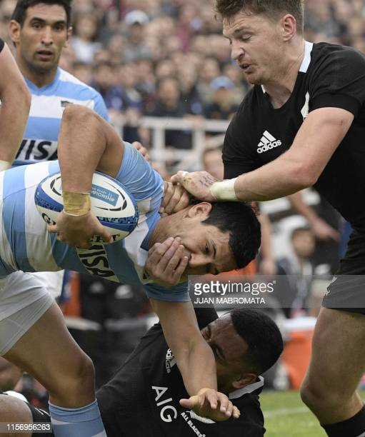 Argentina's Los Pumas wing Matias Moroni is tackled by New Zealand's All Blacks flyhalf Beauden Barrett and centre Ngani Laumape during their Rugby...