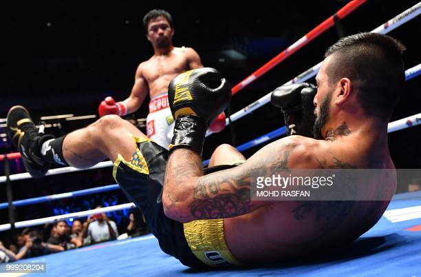 TOPSHOT Argentina's Lucas Matthysse reacts after he was knocked down by Philippines' Manny Pacquiao during their world welterweight boxing...