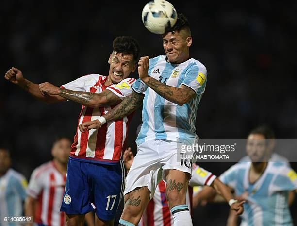Argentina's Marcos Rojo jumps for the ball with Paraguay's midfielder Hernan Perez during their Russia 2018 World Cup qualifier football match in...