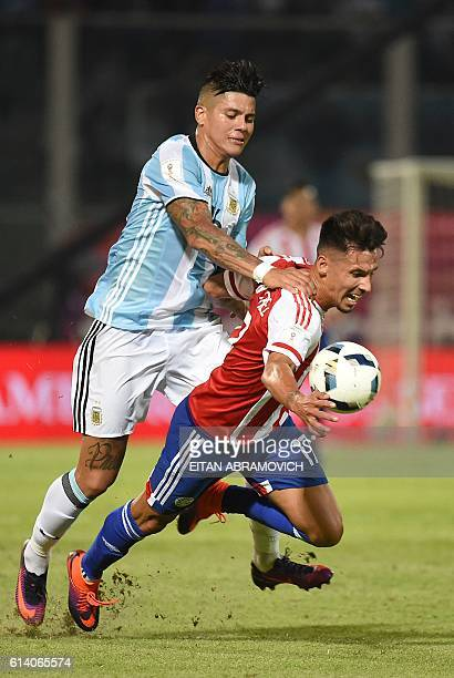 Argentina's Marcos Rojo vies for the ball with Paraguay's midfielder Hernan Perez during their Russia 2018 World Cup qualifier football match in...