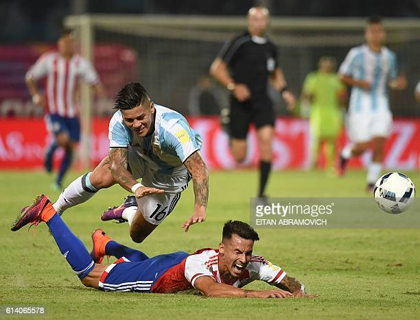 Argentina's Marcos Rojo vies for the ball with Paraguay's midfielder Hernan Perez during their Russia 2018 World Cup football qualifier match in...